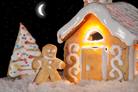 Gingerbread man cookie standing in snow beside house  Moon and stars in the sky  Christmas decoration  Stock Photo