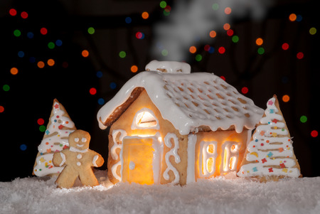 Gingerbread house with gingerbread man and christmas trees  Gingerbread man cookie standing in snow beside house  Christmas decoration