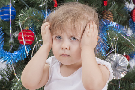Portrait of upset and distraught screaming little girl in white T-shirt near the Christmas tree  Christmas time, New Year