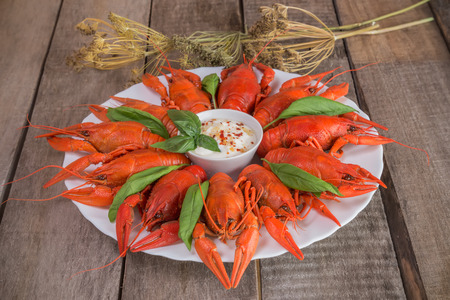 Plate with red boiled crayfish and herbs with white sauce on the side on a wooden table, background in rustic style, selective focus on one crawfish Stock Photo
