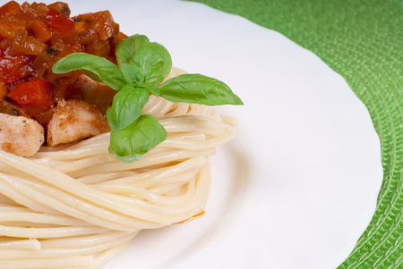 Plate with spaghetti, sauce and basil on green napkin. Chicken in sweet and sour sauce with pineapple and pasta. Stock Photo
