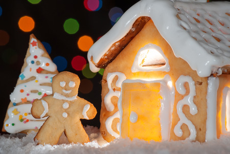 Gingerbread house with gingerbread man and christmas trees. Gingerbread man cookie behind the door. Christmas decoration.