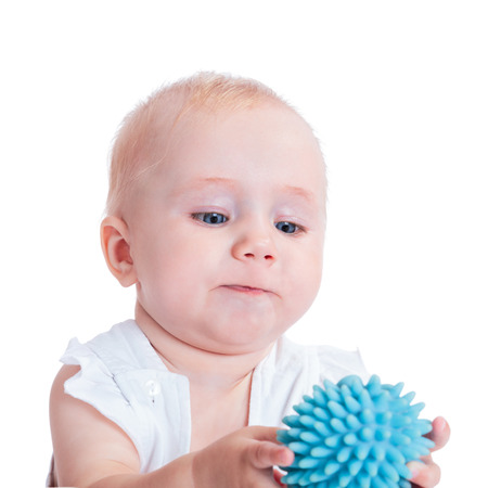 12 18 months: Portrait of a beautiful little girl holding a blue toy into arms. Isolated on white.