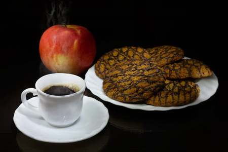 White cup of hot coffee, cookies and red apple and on table with glass surface. The morning breakfast concept.  Black background. Selective focus on cup.
