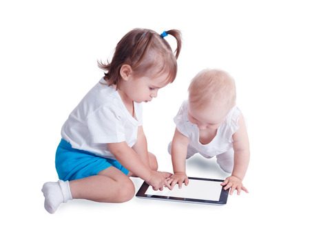 Two little kids playing with tablet PC computer, isolated on white background. Baby hand pointing on  touch screen. Stock Photo