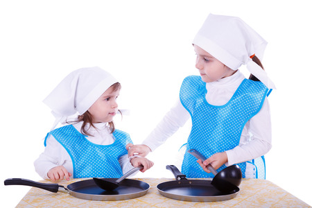 Little children with pans. Two cute girls playing as chefs. Isolated on a white background. photo