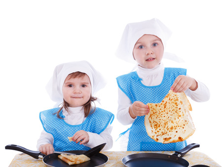 Little children with pancakes. Two cute girls playing as chefs. Surprise for Mothers Day. Isolated on a white background.