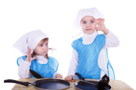 Little children with pans. Two cute girls playing as chefs. One girl gesturing good or delicious. Isolated on a white background. Stock Photo