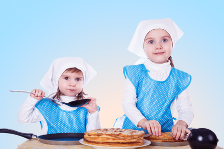 Little children with pancakes. Two cute girls playing as chefs. Surprise for Mothers Day. Blue background. photo