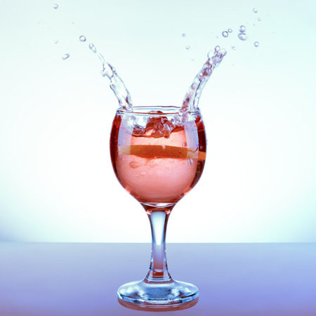 pouring wine: Glass refreshing rose punch with lemon slice and two opposite splashes
