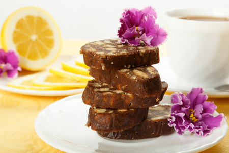 Pile of delicious chocolate cake slices with the cookies filling, decorated violet flowers on a white plate with lemon and cup of tea.
