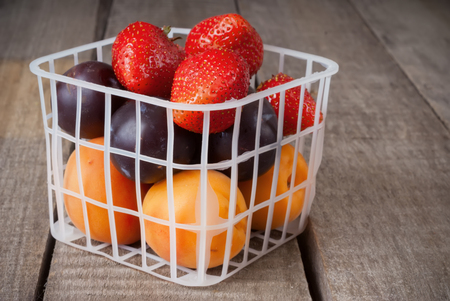 Fresh fruits and strawberry in small plastic basket on wooden background Banco de Imagens