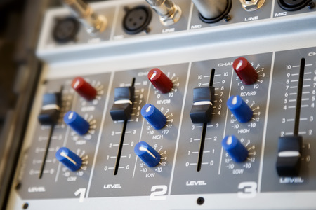Part of an audio sound mixer console with buttons and sliders. Modern equipment for the music.