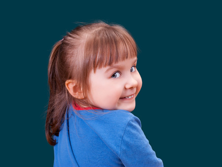 Portrait of happy turning around and smiling little girl on dark green background. Cheerful kid. Stock Photo