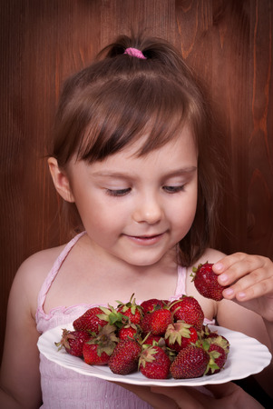 Portrait of the happy little girl eating strawberries