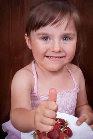 tumb: Portrait of the happy little girl with tumb up gesturing that the strawberry is very good Stock Photo