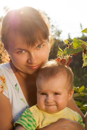 Portrait of young mother with a little baby in the sunny garden. Happy childhood and parenthood.