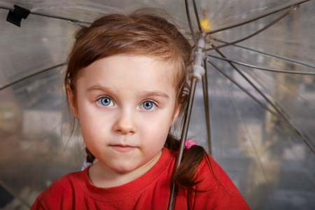 Portrait of little cute girl in red T-shirt holding an umbrella