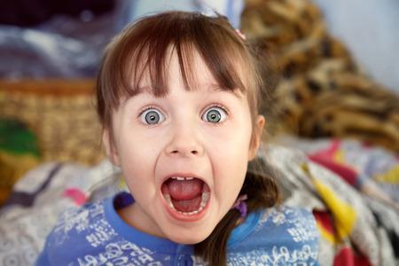 Geschokt gillend meisje met geopende mond in haar slaapkamer