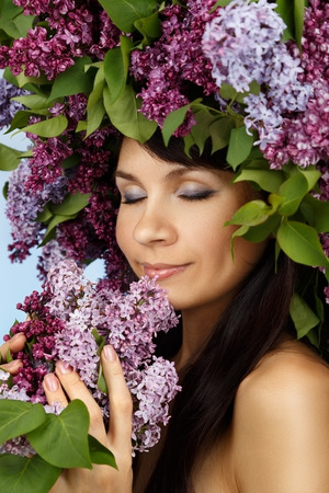 Beautiful young model woman with lilac bouquet and wreath as flowers hair style sniffs the sweet smell of aroma on blue background Stock Photo
