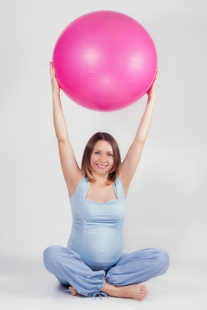 Pretty pregnant woman doing exercise with big gymnastic ball