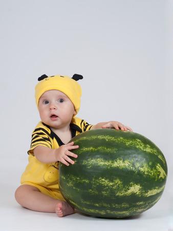 surprised baby: Surprised baby girl sitting behind the big watermelon
