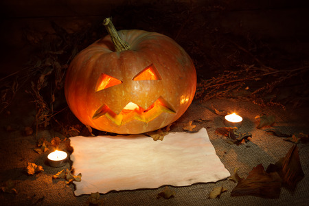 Scary Halloween pumpkin and old burned paper ad layout with candlelight and autumn leafs. Still life. Wooden background.