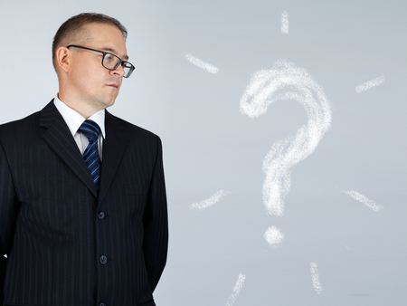 Businessman is thinking and looking at chalk drawn question mark over gray background photo