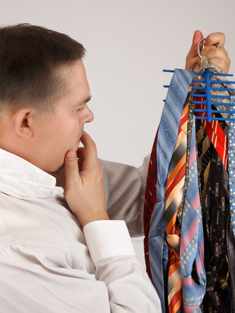Undecided young businessman looking to a lot of neckties, thinking what tie to choose photo
