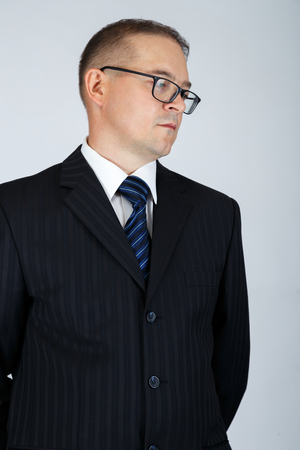 Young serious business man thinking to make a decision. Studio portrait, gray background. photo