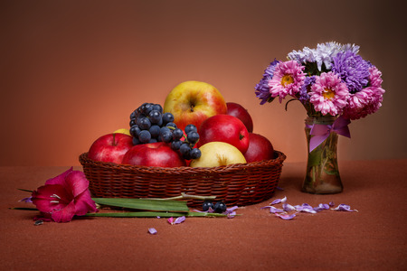 Autumn still life with apples, grape and bouquet of flowers in glass vase