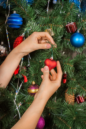Female hands decorating christmas tree with toy red heart. Christmas mood. Winter holidays.