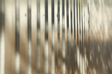 Corrugated metal fence with zinc coating in perspective as a background, shallow depth of field
