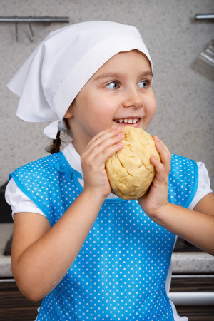 Happy little girl with a dough in a kitchen