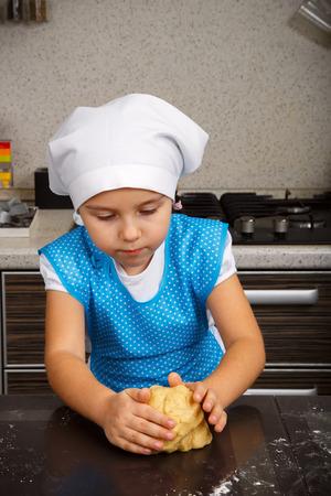 little dough: Little girl is kneading a dough in a kitchen