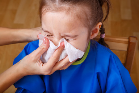 blows: Parent hand helping the playing little girl to blow her nose with a hygienic wet wipe. Seasonal sickness.