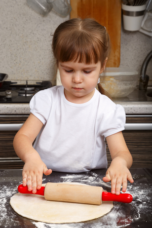 rollingpin: Little girl with a dough and rolling-pin in a kitchen Stock Photo