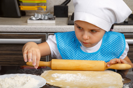Little girl is playing as a cook with a dough and rolling-pin in a kitchen