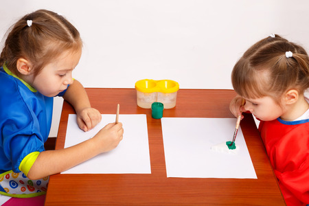 Two cute little girls are painting with gouache while sitting at table