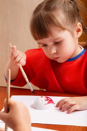 Cute little girl is painting with gouache while sitting at table