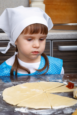 Little girl with a dough in a kitchen