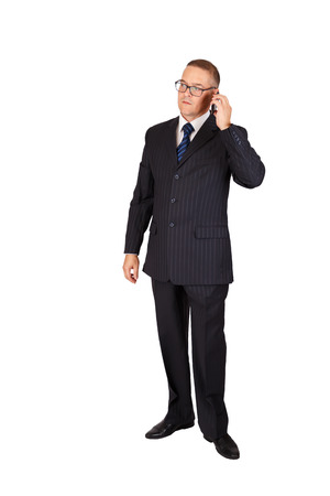 Businessman with serious face in suit and eyeglasses speaking on the cellphone, full length portrait isolated over white background Stock Photo