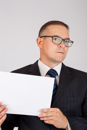 Business man holding white blank paper sheet with copy space ready for your text or letters. Gray background. Stock Photo