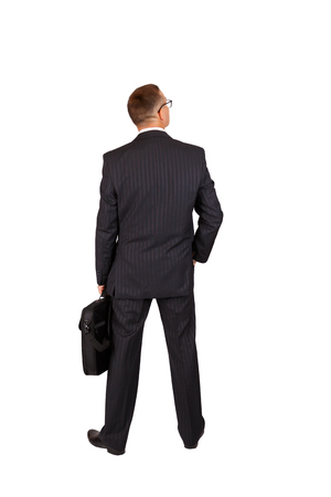 Back view of a walking business man with a notebook case and looking to a side, full length portrait isolated on white background photo