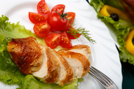 Sliced roasted chicken breast and served with fresh vegetables on white plate close up
