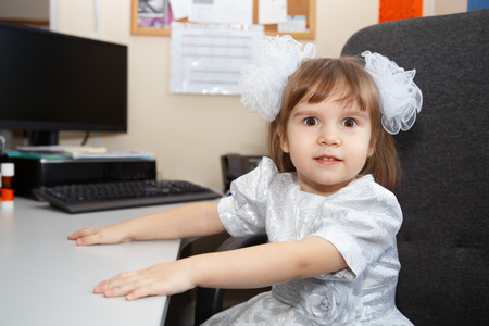 Portrait of the cute little excited girl with white bows sitting at the work desk with computer on an armchair Stock Photo