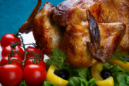 Whole roasted chicken served with fresh vegetables on white plate close up Stock Photo