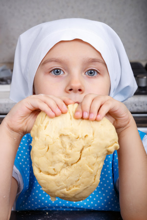Cute little girl with a dough in a kitchen