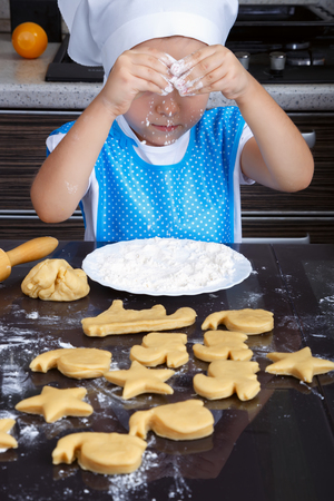 Cute little girl playing with a flour while making cookies in a kitchen Stock Photo