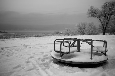 riverside landscape: Childrens playground covered in snow, winter riverside landscape, overcast sky Stock Photo